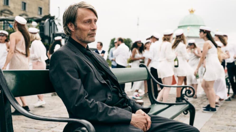 Personagem do filme Druk, de terno preto, sentado em um banco e com expressão séria. Ao fundo, pessoas vestidas de branco.