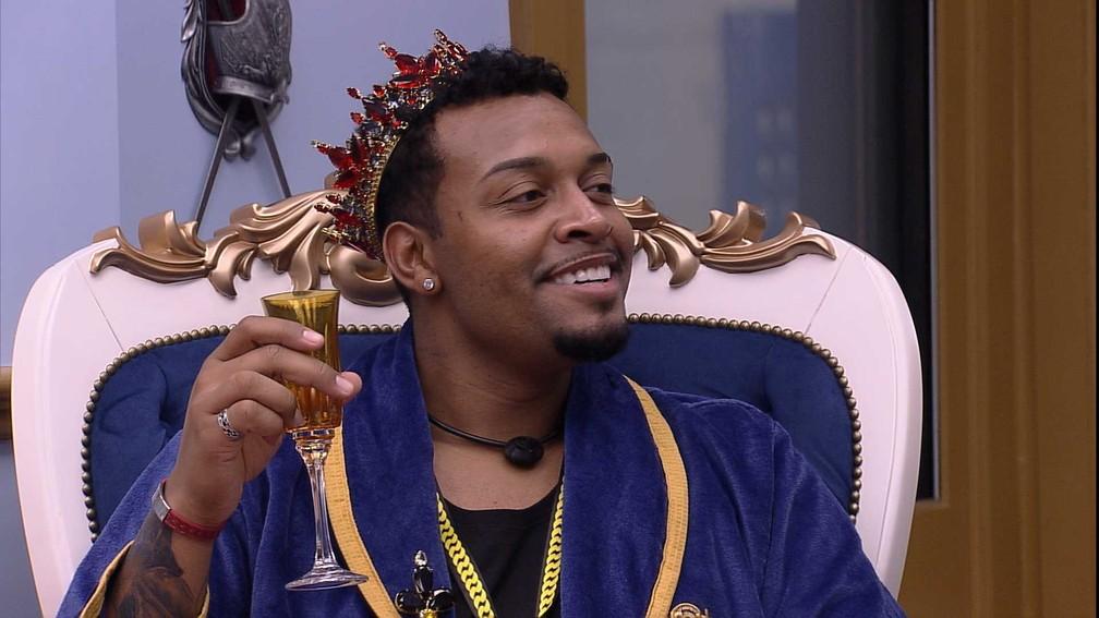 Nego Di no quarto do líder com uma taça na mão, usando roupão azul e dourado e uma coroa vermelha e dourada.]