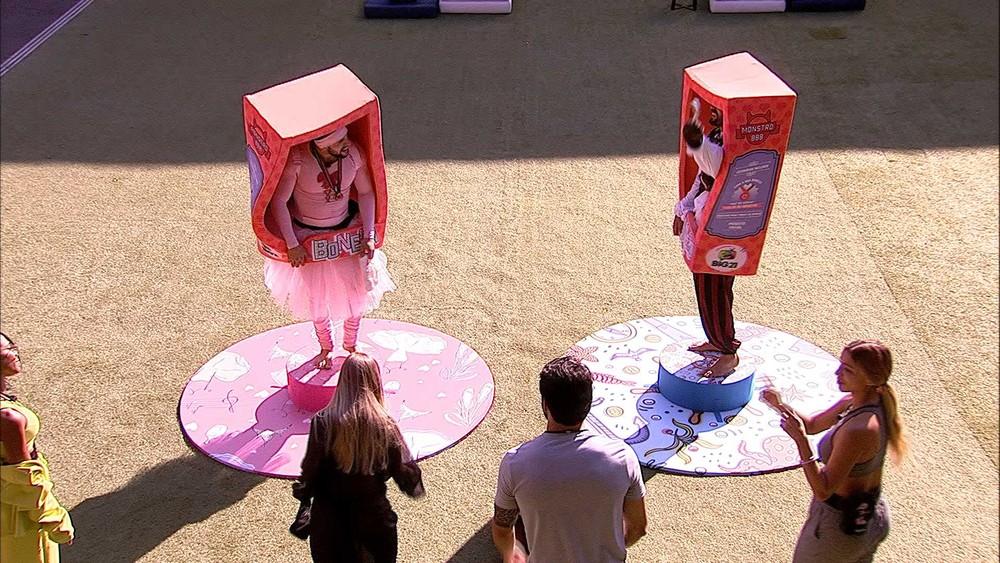 Arthur e Arcrebiano, vestidos de boneca e pirata dentro de uma caixa, em pé em cima de pequenos palcos, com participantes em volta olhando.