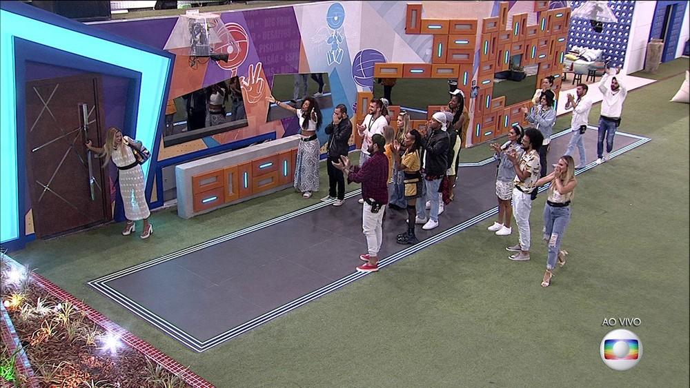 Kerline saindo pela porta da casa, com os outros participantes se despedindo e batendo palmas.