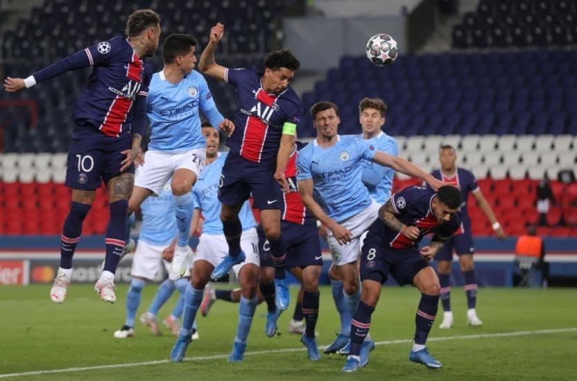 Jogadores do Paris Saint Germain e Manchester City disputam a bola área em jogo da Champions League