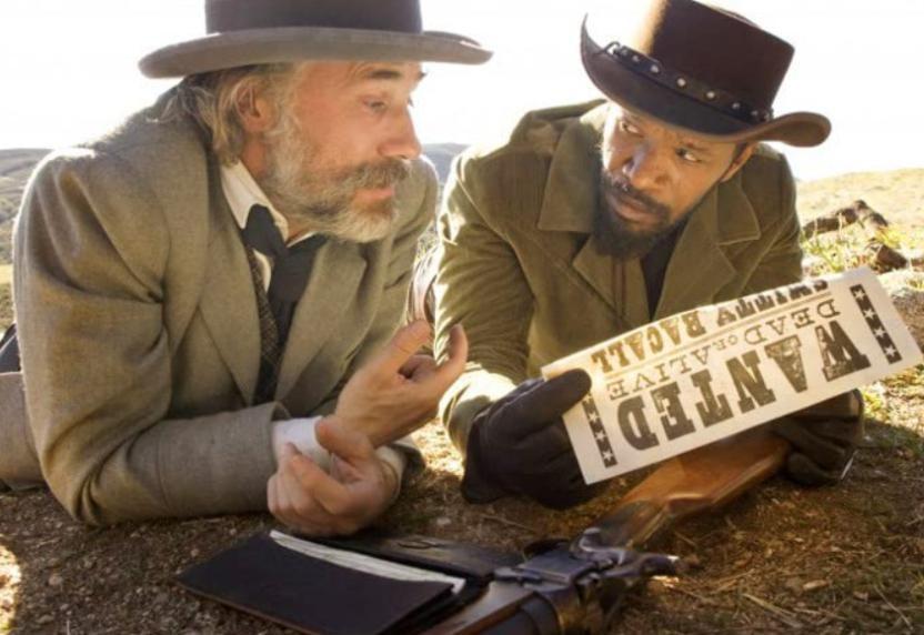 Personagem Dr. King Schultz conversando com Django, que segura um cartaz de procurado.