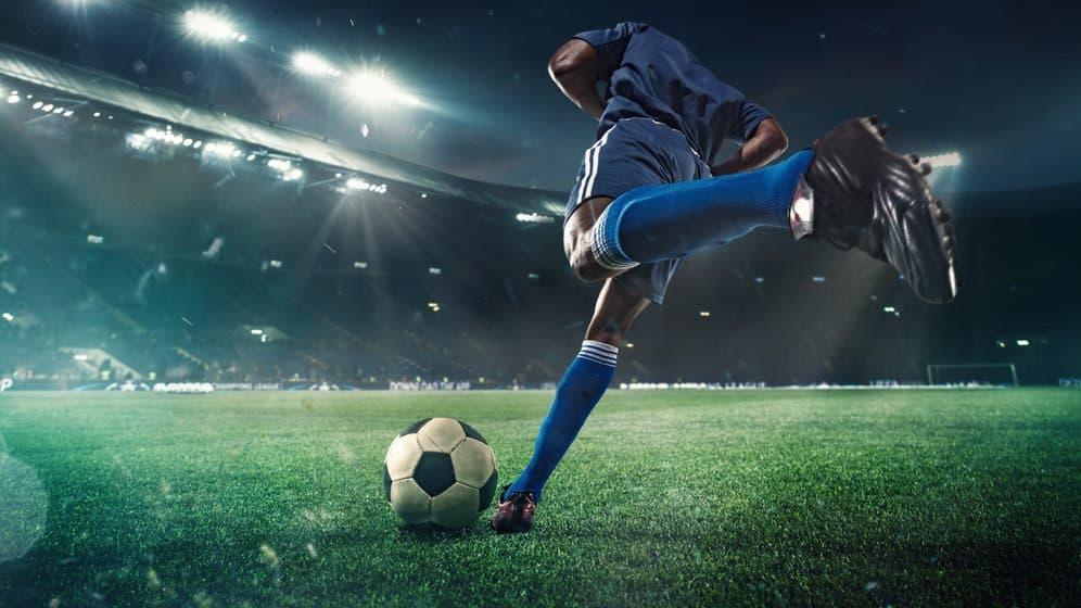 Jogador chutando a bola em um estádio de futebol à noite.