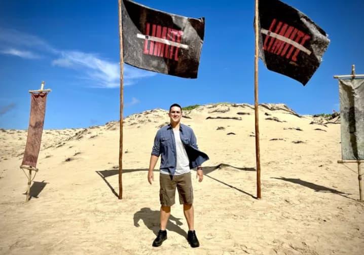 André Marques no cenário do reality show No Limite em meio as dunas de areia.