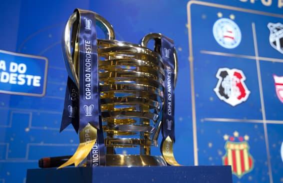 Taça da Copa do Nordeste em cima de um balcão azul e em frente a um fundo azul com os símbolos dos times participantes